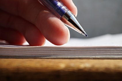 Male hand holding a sharp blue office pen and writing to the white lined notepad as a symbol of taking notes or business communication
